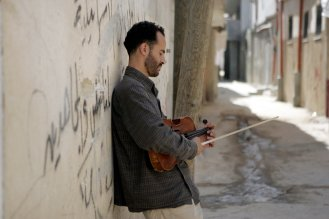 © Georges BARTOLI. Al Kalmanjati le violoniste en arabe est une association franco palestinienne soutenue par le conservatoire d Angers qui a pour but de faire connaitre et d enseigner la musique classique dans les villes et les camps palestiniens. Elle est animee par Ramzi Abredwan gamin de la premiere intifada qui est devenu un virtuose du violon alto en France et qui revient regulierement avec des musiciens etrangers en Palestine rencontrer des enfants. Ramzi Aburedwan dans les rues du camp de refugies de El Amari a Ramallah ou il a grandi.